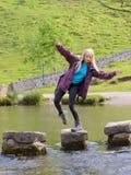 Ung kvinna som faller från att kliva stenar Royaltyfria Bilder