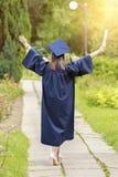 Ung kvinna som firar avläggande av examendagen arkivbild