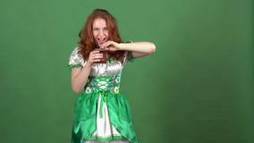 Ung kvinna som firar dag för St Patrick ` s på den gröna väggen som bär den traditionella klänninginnehavkrukan med pengar lager videofilmer