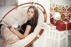 Ung kvinna som firar julhelgdagsafton med närvarande gåvor Fotografering för Bildbyråer