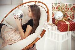 Ung kvinna som firar julhelgdagsafton med närvarande gåvor Arkivbild