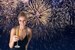 Ung kvinna som firar med champagne i henne händer fotografering för bildbyråer