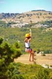 Ung kvinna som flyger ner på zipline i berget, extrem sport Arkivbilder