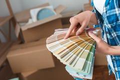 Ung kvinna som flyttar sig till ett nytt ställeanseende som väljer färg från palettnärbild royaltyfria foton