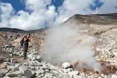 Ung kvinna som fotograferar röka fumarolen på den aktiva vulkan för krater Fotografering för Bildbyråer