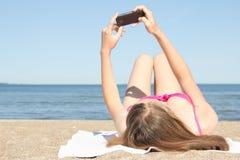Ung kvinna som fotograferar sig med mobiltelefonen på stranden Arkivbilder