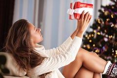 Ung kvinna som framme kopplar av på stol av julgranen royaltyfri fotografi