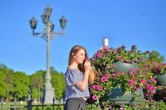 Ung kvinna som framme luktar blomman i blomsterrabatten av en anci arkivbilder
