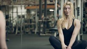 Ung kvinna som framme sitter av spegeln på golvidrottshall lager videofilmer