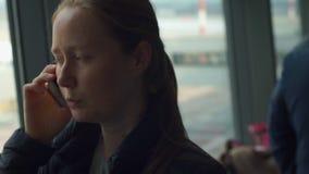 Ung kvinna som framme talar på en mobiltelefon av ett stort fönster på en flygplats stock video
