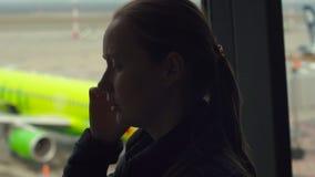 Ung kvinna som framme talar på en mobiltelefon av ett stort fönster på en flygplats arkivfilmer
