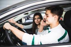 Ung kvinna som framme visar en väg av bilen medan chauffören som använder en mobiltelefon och förlorar koncentration farlig körni fotografering för bildbyråer