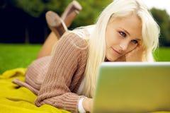 Ung kvinna som fungerar på henne anteckningsboken i park Fotografering för Bildbyråer