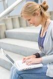 Ung kvinna som fungerar på henne bärbar datordatoren Arkivbild