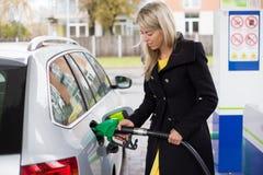 Ung kvinna som fyller på bensin i bensinstation Arkivfoto