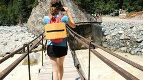 Ung kvinna som går över träbron över bergfloden royaltyfria bilder