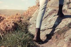 Ung kvinna som går i bergen Arkivfoton