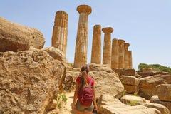 Ung kvinna som går i dalen av templen Agrigento, Sicilien Handelsresandeflickan besöker grekiska tempel i sydliga Italien arkivfoto