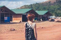 Ung kvinna som går i en liten stad i u-land Arkivbild