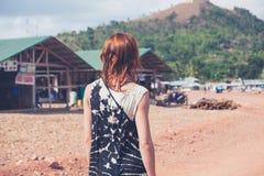 Ung kvinna som går i en liten stad i u-land Royaltyfri Fotografi