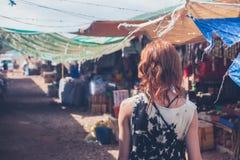 Ung kvinna som går i en liten stad i u-land Fotografering för Bildbyråer