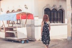 Ung kvinna som går i en liten stad i u-land Royaltyfri Bild