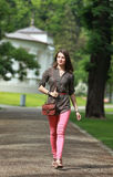 Ung kvinna som går i en parkera royaltyfria bilder