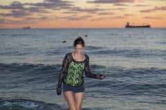 Ung kvinna som går i havet Arkivfoton