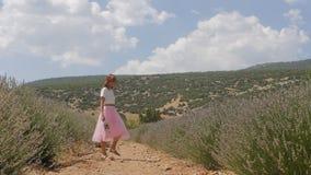 Ung kvinna som går i lavandafältet arkivfilmer