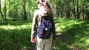 Ung kvinna som går i skogen lager videofilmer