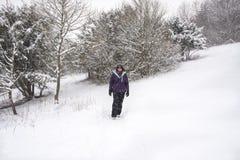 Ung kvinna som går i snön Arkivfoto