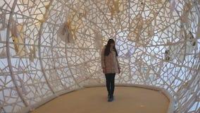Ung kvinna som går inom av samtida konstobjekt på museet Undersökande modern konst för flicka lager videofilmer