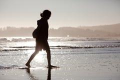 Ung kvinna som går längs strand Royaltyfri Fotografi