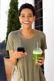 Ung kvinna som går med mobiltelefon- och fruktfruktsaft Royaltyfri Bild