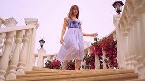Ung kvinna som går ner trappan stock video