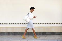 Ung kvinna som går och överför textmeddelandet på mobiltelefonen Royaltyfri Fotografi