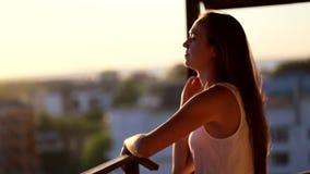 Ung kvinna som går på balkongen som håller ögonen på solnedgången, mittskott arkivfilmer