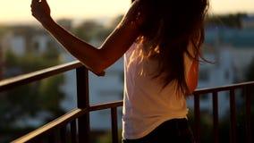 Ung kvinna som går på balkongen som håller ögonen på solnedgången, mittskott lager videofilmer