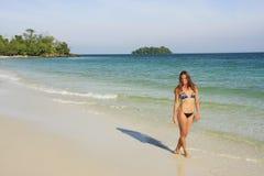 Ung kvinna som går på en strand av den KohRong ön, Cambodja Royaltyfri Foto
