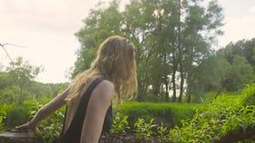 Ung kvinna som går på en trädfilial lager videofilmer