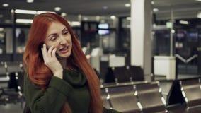 Ung kvinna som g?r p? flygplatsterminalen och talar p? telefonen