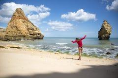 Ung kvinna som går på korsstenar på stranden royaltyfria bilder