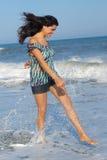 Ung kvinna som går på strand arkivbild