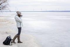 Ung kvinna som går på stranden som håller ögonen på det djupfrysta vattnet och det varma teet för drinkar Royaltyfri Foto