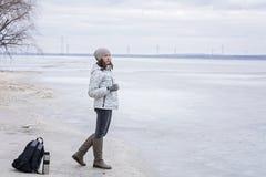 Ung kvinna som går på stranden som håller ögonen på det djupfrysta vattnet och det varma teet för drinkar Royaltyfri Bild