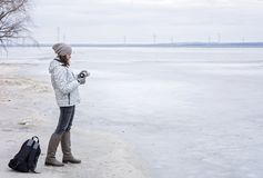 Ung kvinna som går på stranden som håller ögonen på det djupfrysta vattnet och det varma teet för drinkar Royaltyfria Bilder