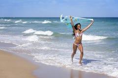 Ung kvinna som går på stranden med en kulör sarong royaltyfri bild