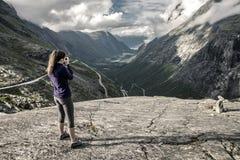 Ung kvinna som går runt om Trollstigen, Norge Arkivbilder
