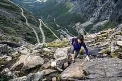 Ung kvinna som går runt om Trollstigen, Norge Arkivbild