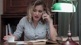 Ung kvinna som går till och med en bok och har ett ilsket sammanträde för telefonkonversation på hennes skrivbord royaltyfri foto